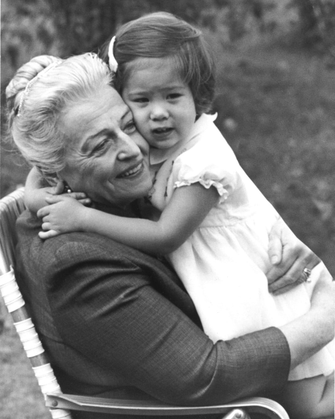 Pearl Buck hugging little girl sitting on her lap