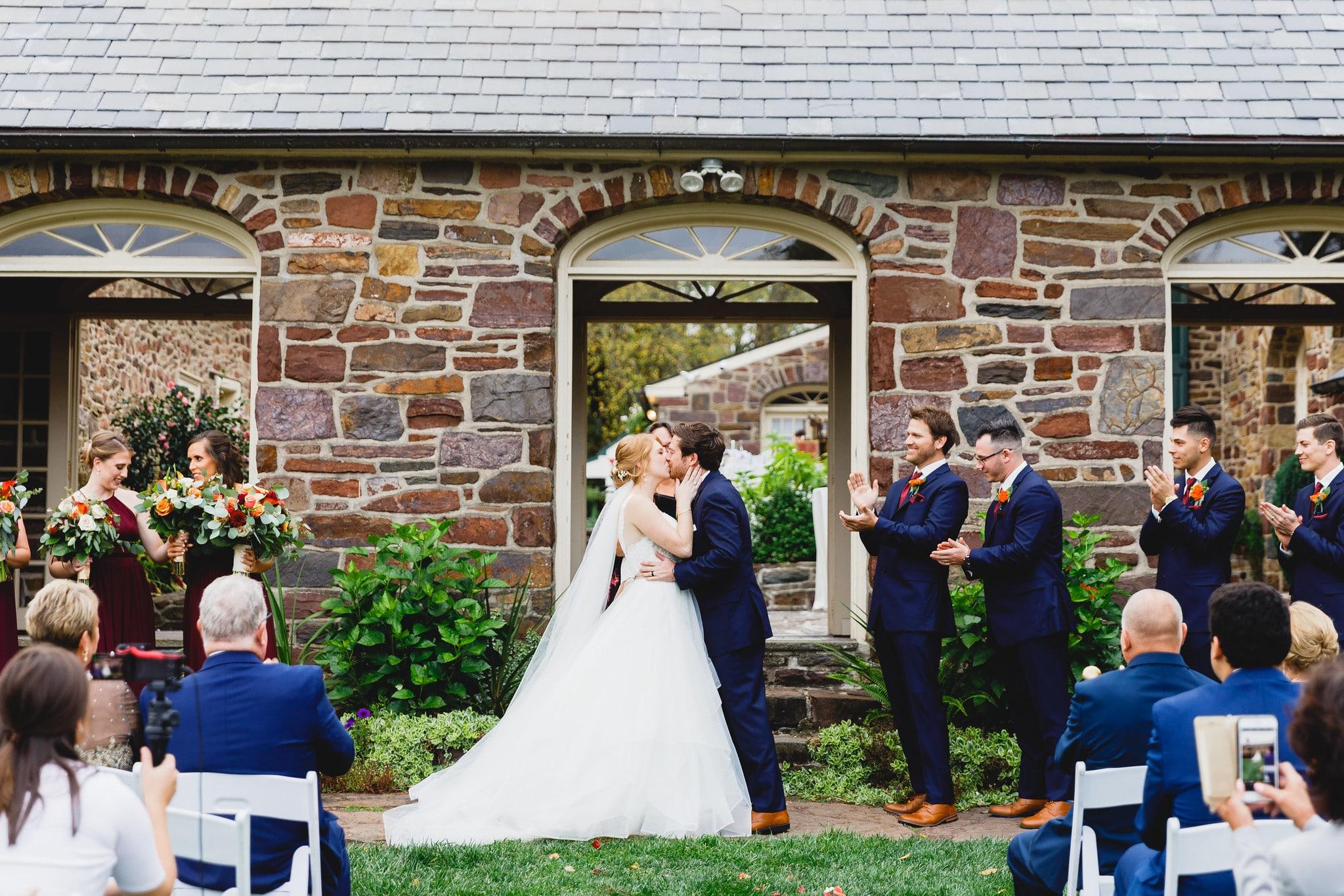 Bride and groom kiss outside Pearl Buck House