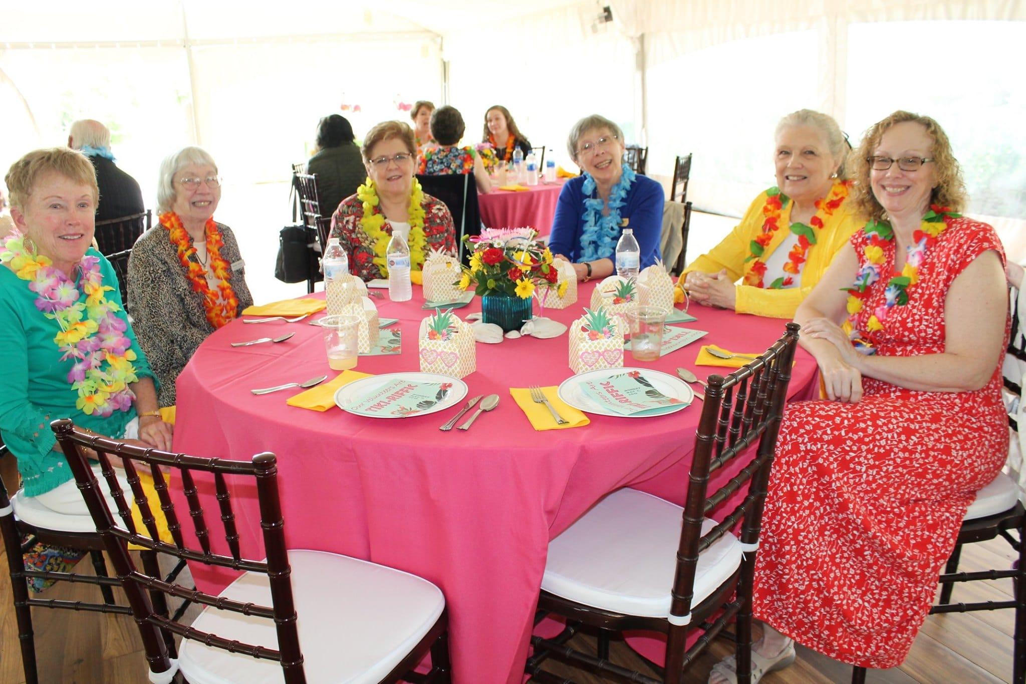 Women wearing leis at Volunteer Appreciation Luncheon
