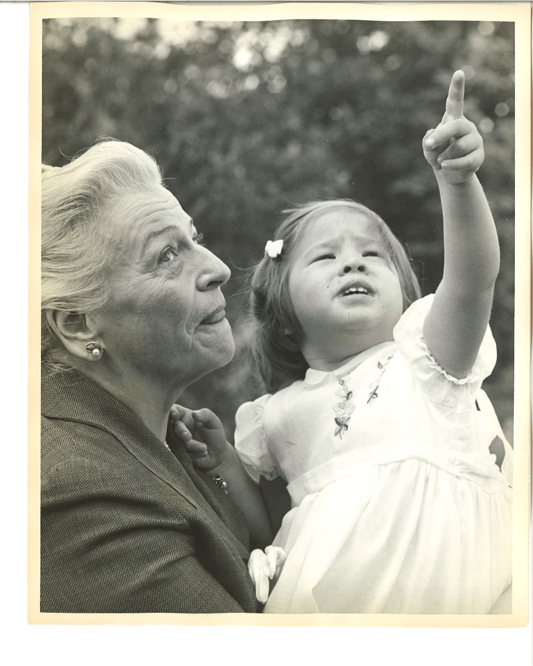 Pearl Buck sitting with child pointing at the sky