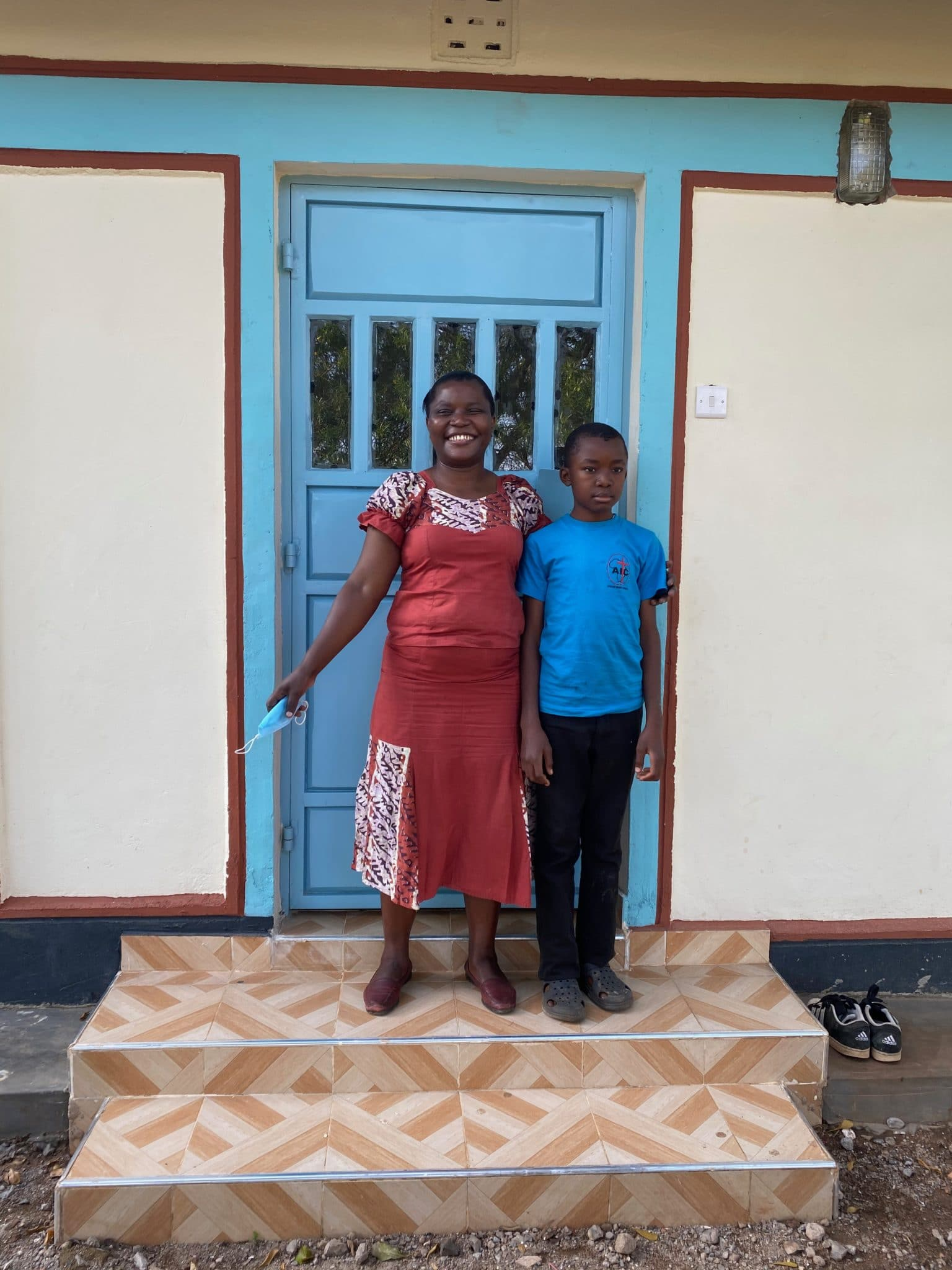 Family in Kenya standing in front of their house